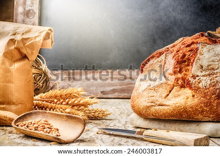 Freshly baked bread in rustic setting with copyspace on blackboard - stock photo