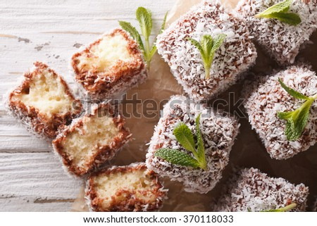 Freshly baked cakes Lamington decorated coconut close-up on the table. horizontal view from above