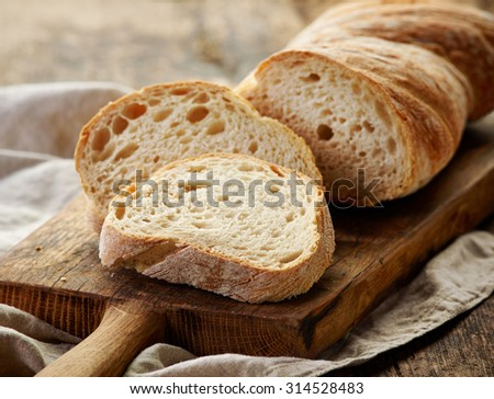 freshly baked ciabatta bread on wooden cutting board - stock photo