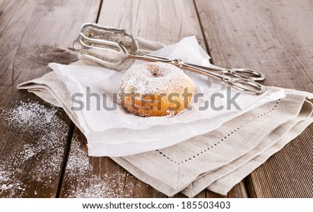 Freshly baked cinnamon sugared doughnuts on baking paper and linen napkin with silver vintage cake tongs on  wooden background. Elegant rustic still life - stock photo