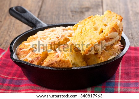 Freshly baked corn bread in cast iron pan - stock photo