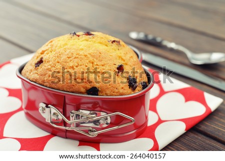 Freshly baked cranberry muffin in shape of heart. - stock photo