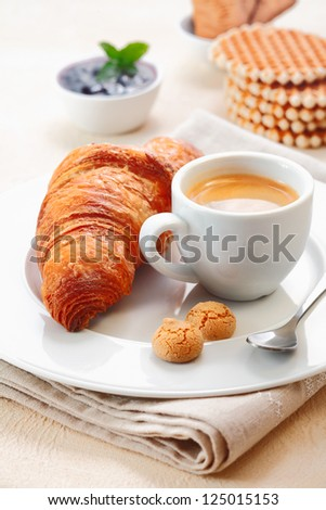 Freshly baked crisp golden croissant served with a cup of rich espresso and two small macaroon biscuits in a restaurant - stock photo