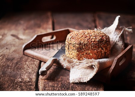 Freshly baked delicious crusty wholewheat seed bread served on a rustic cloth and wooden tray for a wholesome snack - stock photo
