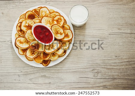 freshly baked fritters on a plate and strawberry jam on a wooden background. top view. copy space background - stock photo