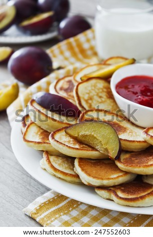 freshly baked fritters on a plate, strawberry jam, ripe plums and milk on the table. traditional european cuisine. selective focus - stock photo