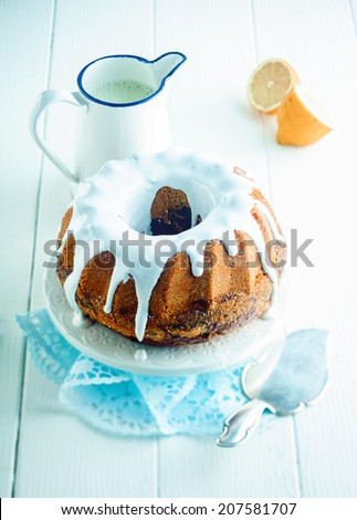 Freshly baked glazed lemon ring cake served on a cake stand for dessert with a jug of tangy citrus sauce and a spatula to serve, high angle view - stock photo