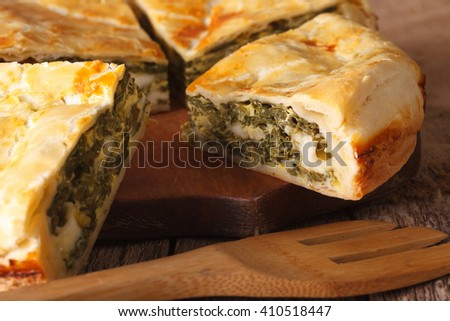 Freshly baked Greek pie with spinach on the table macro. horizontal