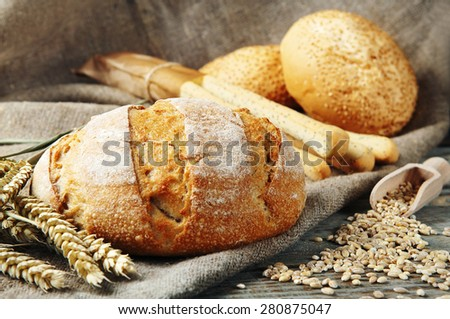 freshly baked, homemade bread on a wooden table. Next to the bread two whole eggs, scattered the seeds of wheat, two buns with sesame seeds and bread sticks with poppy seeds. rustic style. closeup  - stock photo