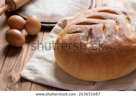 Freshly baked homemade bread on rustic wooden table. Round board with flour, eggs and rolling pin on background. still life with backlight natural lighting. Shallow focus - stock photo