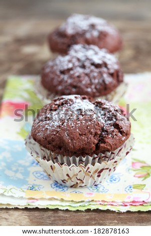 Freshly baked homemade chocolate muffins with powdered sugar on the wooden table, selective focus - stock photo