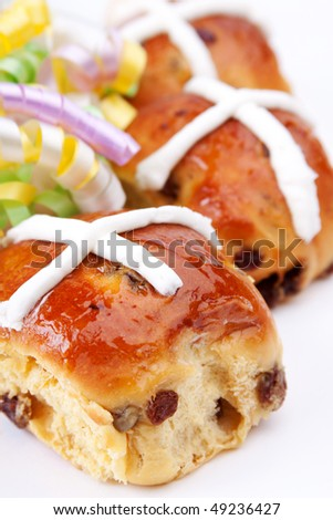 Freshly baked hot cross buns for Easter celebrations. Colorful spring ribbons in background. Selective focus. - stock photo