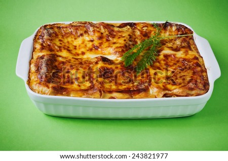 freshly baked lasagna in a ceramic baking dish on a green background. traditional cuisine europe - stock photo