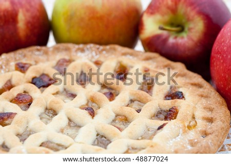 Freshly baked lattice apple pie with apples in the background - stock photo