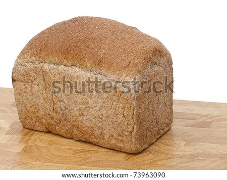 Freshly baked loaf of brown, wholemeal bread on a cutting board against a pure white background - stock photo