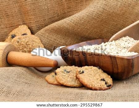 Freshly baked oatmeal raisin cookies on burlap.  Oats, eggs and a rolling pin complete the image. - stock photo