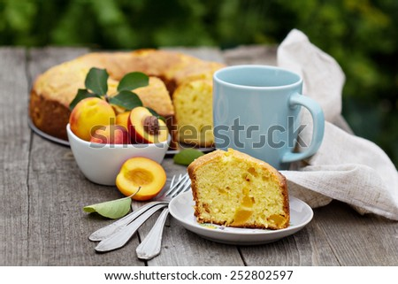 Freshly baked peach cake with tea outdoors - stock photo