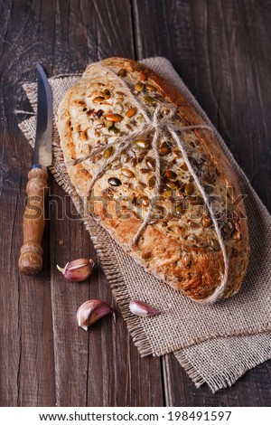 Freshly baked rustic sourdough bread with seeds and grains over dark wooden background. Selective focus, Shallow DoF, dramatic lighting - stock photo