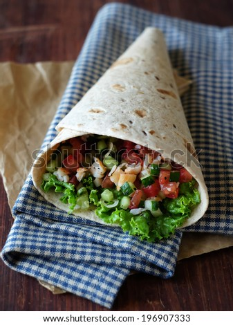 Freshly baked tortilla wrap with cucumbers, tomatoes, lettuce, prawns, avocado and bell pepper for breakfast or summer picnic snack - stock photo