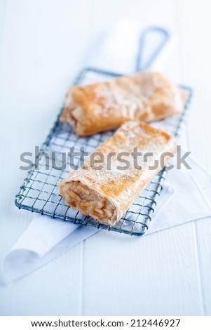 Freshly baked traditional German apfelstrudel or apple strudel on a wire rack on a high key white wooden background with copyspace - stock photo