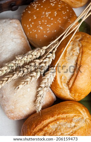 Freshly baked traditional rolls on cotton cloth with ears of wheat grain - stock photo