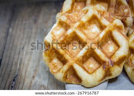 freshly baked waffles on a wood background - stock photo