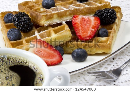 Freshly baked waffles with berries and coffee - stock photo