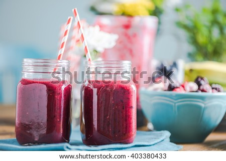 Freshly blended smoothie, in sunny kitchen on farmhouse table. Negative space for text, ingredients and fresh fruits in background. - stock photo