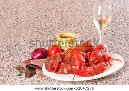 Freshly boiled lobster on a white plate with crackers, tomato, an onion a glass of wine and a napkin on a granite counter - stock photo