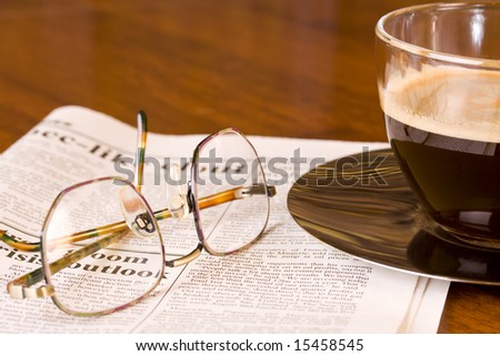 freshly brewed coffee on a newspaper with a pair of spectacles on a wooden desk - stock photo