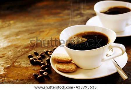 Freshly brewed espresso coffee served in a stylish modern cup with two cookies on a wooden table with scattered coffee beans and copy space - stock photo
