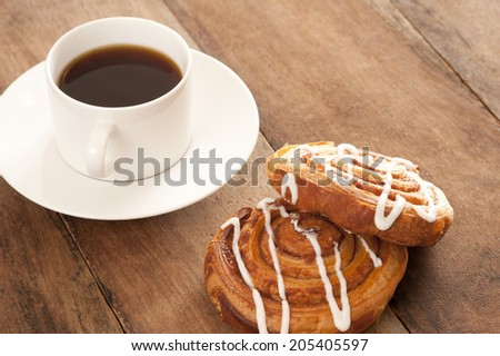 Freshly brewed full roast cup of filter or espresso coffee served with flaky fruity Danish pastries drizzled with icing sugar for a tasty coffee break - stock photo
