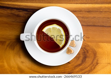Freshly brewed white cup and saucer of healthy herbal tea with lemon from above with heart shaped brown sugar cubes on a wooden table - stock photo