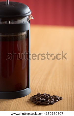 Freshly brewing cafetiere on a kitchen table in a red kitchen with some coffee beans in front of it - stock photo