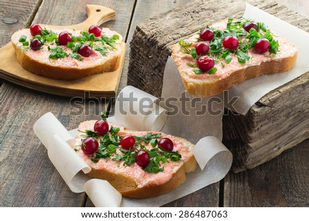 Freshly bruschetta with salmon butter, capelin caviar, cranberry and herbs on a thick wooden board, paper, rustic - stock photo