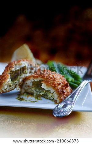 Freshly cooked Chicken Kiev oozing garlic and parsley butter with seasonal vegetables. The perfect image for your bistro or restaurant cover design. Copy space. - stock photo