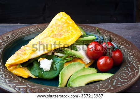 Freshly cooked omelette filled with feta cheese, spinach, avocado and tomato. A healthy vegetarian breakfast served on a rustic plate on a stone slate table. - stock photo