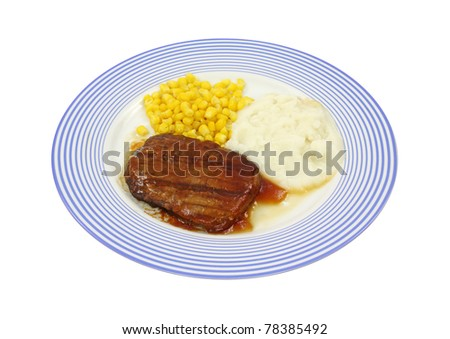 Freshly cooked Salisbury steak frozen dinner with corn and potato on a blue striped plate. - stock photo