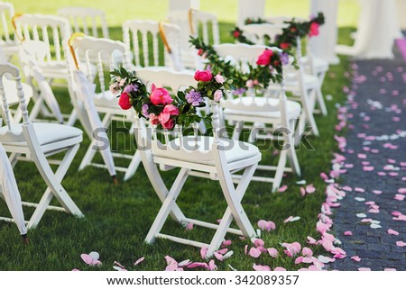 Freshly cut beautiful red and purple wedding flowers garland on chair - stock photo