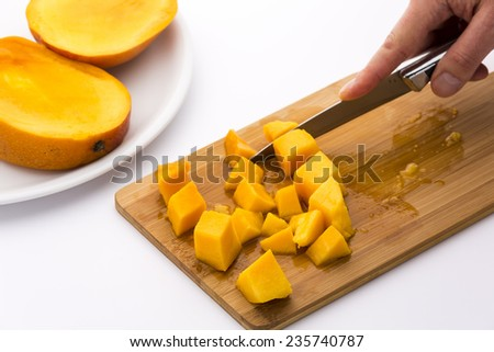 Freshly cut cubes of ripe mango fruit flesh resting on a bamboo cutting board, while a male hand is finishing the last cut with a kitchen blade. Mango juice bedewing the wooden slat. White background. - stock photo