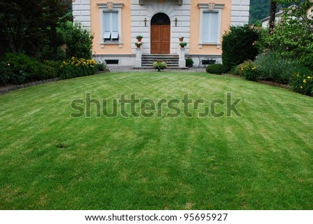 Freshly cut lawn in garden in front of a beautiful ancient villa, Italy - stock photo