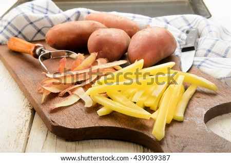 freshly cut raw french fries on a wooden board and peeler - stock photo