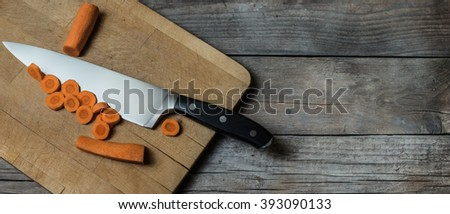 freshly cutted carrots on old wooden table background with knife  - stock photo