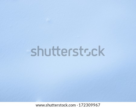 Freshly fallen snow on the ground during a sunny day - stock photo