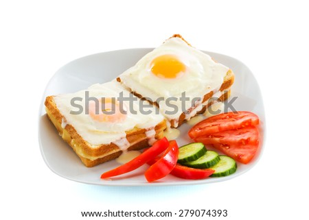 Freshly fried eggs on white plate with vegetables, cheese and toast. - stock photo
