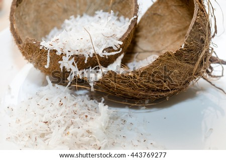 Freshly grated coconut in shell on white table. Coconut flakes in broken coconut. - stock photo