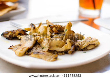 Freshly grilled oyster mushrooms sit on a white plate. - stock photo