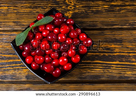 Freshly harvested ripe red cherries cleaned and served in a bowl for a healthy sweet or summer dessert, high angle view on a rustic wooden background with wood grain texture - stock photo