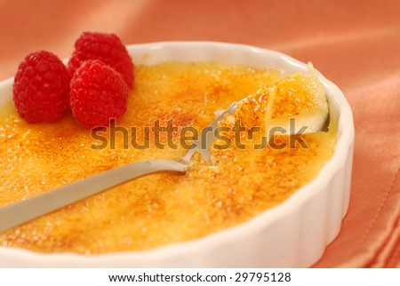 Freshly made delicious creme brulee with raspberries - stock photo