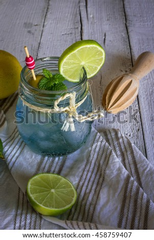 freshly made drink gin and tonic with lime and cucumber slices and mint on old wooden table - stock photo